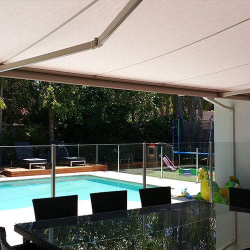 A retractable awning from The Blind Shop in Canberra overlooking a backyard pool