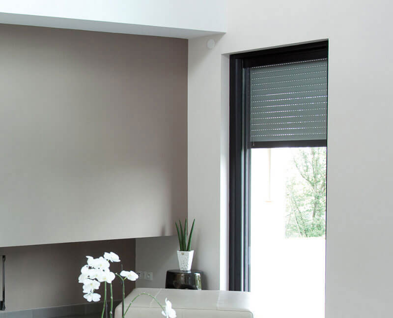 A portrait image of roller shutters being used in a modern, Canberra loungeroom. Get yours from The Blind Shop today!