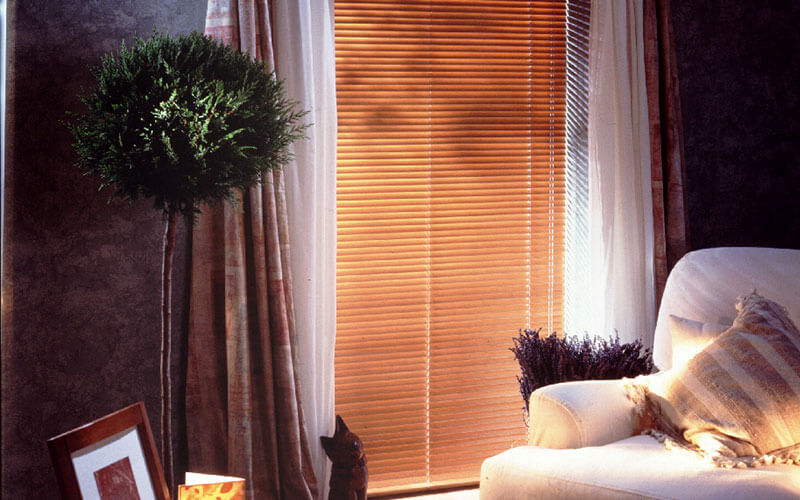 A light filtered loungeroom with timber venetian blinds. Get yours from the Blind Shop in Canberra