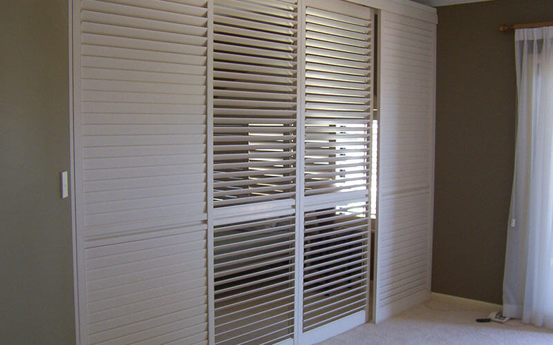 White vogue shutters in a bedroom. Order yours from The Blind Shop in Canberra!